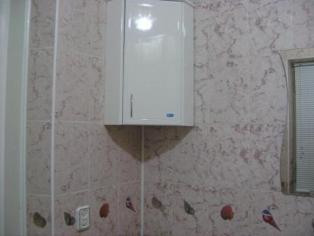 Практичный угловой навесной шкаф, размещенный в ванной
